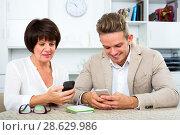 Купить «Mother and son with smartphones», фото № 28629986, снято 8 июля 2020 г. (c) Яков Филимонов / Фотобанк Лори