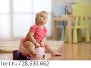 funny baby sitting on chamber pot with toilet paper roll. Стоковое фото, фотограф Оксана Кузьмина / Фотобанк Лори