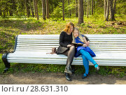 Купить «Embracing daughter and mum read interesting book in a park», фото № 28631310, снято 21 мая 2017 г. (c) Сергей Дубров / Фотобанк Лори