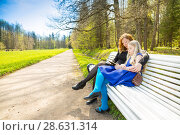 Купить «Blonde school-aged girl with mother sitting in spring park and read interesting book», фото № 28631314, снято 21 мая 2017 г. (c) Сергей Дубров / Фотобанк Лори