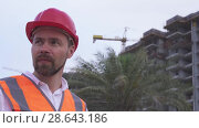 Купить «Man in a helmet, architect, engineer, manager tells about the progress of construction in evening stock footage video», видеоролик № 28643186, снято 23 июня 2018 г. (c) Юлия Машкова / Фотобанк Лори