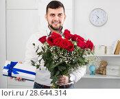 Купить «Positive young man congratulating woman with bouquet», фото № 28644314, снято 5 марта 2017 г. (c) Яков Филимонов / Фотобанк Лори