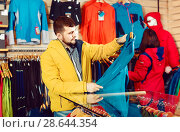 Купить «Couple examining track jackets in sports clothes store», фото № 28644354, снято 8 марта 2017 г. (c) Яков Филимонов / Фотобанк Лори