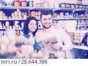 Купить «Couple choosing brush for house decoration», фото № 28644386, снято 9 марта 2017 г. (c) Яков Филимонов / Фотобанк Лори