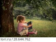 Купить «Маленькая девочка читает книгу в саду», фото № 28644762, снято 18 июня 2018 г. (c) Julia Shepeleva / Фотобанк Лори