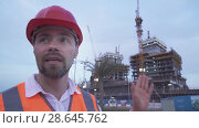 Купить «Man in a helmet, architect, engineer, manager tells about the progress of construction in evening stock footage video», видеоролик № 28645762, снято 23 июня 2018 г. (c) Юлия Машкова / Фотобанк Лори