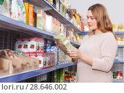 Купить «Smiling woman buyer with assortment of grocery food store», фото № 28646002, снято 11 апреля 2018 г. (c) Яков Филимонов / Фотобанк Лори
