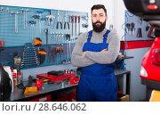 Купить «Young man worker displaying his workplace in motorcycle workshop», фото № 28646062, снято 14 августа 2018 г. (c) Яков Филимонов / Фотобанк Лори