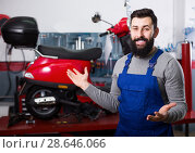 Купить «Worker demonstrating motorbikes in motorcycle workplace», фото № 28646066, снято 22 сентября 2018 г. (c) Яков Филимонов / Фотобанк Лори