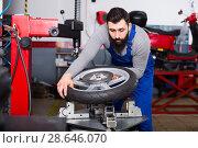 Купить «Man 20-30years old is working at restoring wheel», фото № 28646070, снято 14 августа 2018 г. (c) Яков Филимонов / Фотобанк Лори
