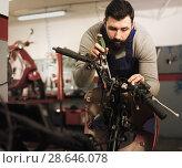 Купить «Worker repairing motorbike», фото № 28646078, снято 14 августа 2018 г. (c) Яков Филимонов / Фотобанк Лори