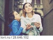 Купить «Mother and daughter consulting guide in phone», фото № 28646102, снято 18 июля 2018 г. (c) Яков Филимонов / Фотобанк Лори