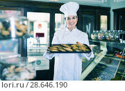 Купить «Woman baker showing warm tasty croissants», фото № 28646190, снято 24 января 2017 г. (c) Яков Филимонов / Фотобанк Лори