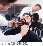 Купить «Ordinary guy creating shape for beard of client», фото № 28646262, снято 27 января 2017 г. (c) Яков Филимонов / Фотобанк Лори