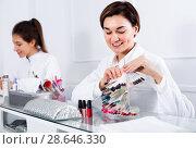 Купить «Female manicurist showing lacquer color schemes», фото № 28646330, снято 2 февраля 2017 г. (c) Яков Филимонов / Фотобанк Лори
