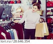 Купить «Female shopper examining warm sweaters in women's cloths shop», фото № 28646354, снято 7 февраля 2017 г. (c) Яков Филимонов / Фотобанк Лори