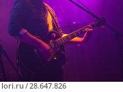 Купить «Guitarist plays on guitar in purple lights», фото № 28647826, снято 11 декабря 2016 г. (c) EugeneSergeev / Фотобанк Лори