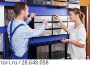Купить «Worker helping woman choosing mailbox», фото № 28648058, снято 17 апреля 2018 г. (c) Яков Филимонов / Фотобанк Лори