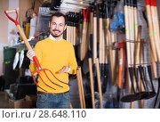 Купить «Adult man choosing new pitchfork», фото № 28648110, снято 2 марта 2017 г. (c) Яков Филимонов / Фотобанк Лори