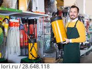 Купить «Laughing guy deciding on best garden sprayer», фото № 28648118, снято 2 марта 2017 г. (c) Яков Филимонов / Фотобанк Лори