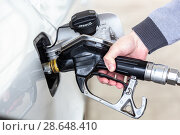 Купить «Closeup of mans hand pumping gasoline fuel in car at gas station.», фото № 28648410, снято 30 апреля 2014 г. (c) Matej Kastelic / Фотобанк Лори
