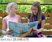 Купить «Веселые девочки-подружки обсуждают книгу на скамейке в парке», фото № 28648678, снято 28 июня 2018 г. (c) Ирина Борсученко / Фотобанк Лори