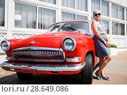 """Счастливая женщина стоит возле автомобиля """"Волга"""" ГАЗ-21 красного цвета (2018 год). Редакционное фото, фотограф Игорь Низов / Фотобанк Лори"""