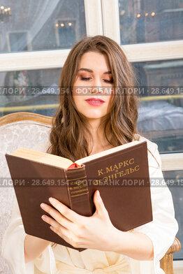 Купить «Young brunette reads writings of Karl Marx and Friedrich Engels», фото № 28649154, снято 1 апреля 2018 г. (c) Сергей Дубров / Фотобанк Лори