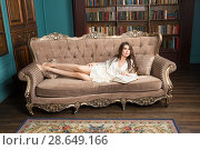 Купить «Long-hair girl wearing nightwear lies on lounge in library and reads a book», фото № 28649166, снято 1 апреля 2018 г. (c) Сергей Дубров / Фотобанк Лори