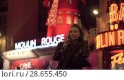 Купить «Woman tourist posing to make best shot near Moulin Rouge in night Paris», видеоролик № 28655450, снято 29 сентября 2017 г. (c) Данил Руденко / Фотобанк Лори