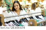 Купить «Portrait of smiling women choosing clothes in the modern shop», видеоролик № 28659674, снято 27 марта 2018 г. (c) Яков Филимонов / Фотобанк Лори