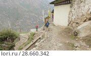 Купить «Tourists walking in nepalese village Prok, trek around mountain Manaslu, Nepal», видеоролик № 28660342, снято 17 июня 2018 г. (c) Dzmitry Astapkovich / Фотобанк Лори
