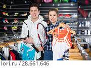 Купить «Female with male are choosing new T-shirt for tennis for him in the speciality store.», фото № 28661646, снято 7 февраля 2018 г. (c) Яков Филимонов / Фотобанк Лори