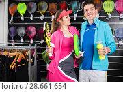 Купить «Sporty couple in sportwear is demonstraiting modern racket and balls for padel», фото № 28661654, снято 7 февраля 2018 г. (c) Яков Филимонов / Фотобанк Лори