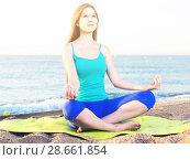 Купить «Female 20-25 years old is sitting and practicing meditation in blue T-shirt», фото № 28661854, снято 4 августа 2017 г. (c) Яков Филимонов / Фотобанк Лори