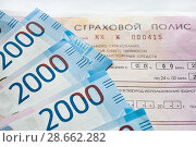 Купить «Страховой полис ОСАГО  и рублевые банкноты», фото № 28662282, снято 24 июня 2018 г. (c) Victoria Demidova / Фотобанк Лори