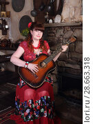 Купить «Красивая цыганка возле камина играет на гитаре», фото № 28663318, снято 13 мая 2018 г. (c) Марина Володько / Фотобанк Лори