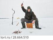 fishing at winter. Fisherman hooking fish on ice. Стоковое фото, фотограф Дмитрий Калиновский / Фотобанк Лори