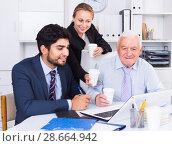 Купить «Employees are demonstrating reports on laptop to mature boss», фото № 28664942, снято 27 июня 2017 г. (c) Яков Филимонов / Фотобанк Лори