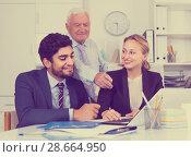 Купить «Employees are demonstrating reports on laptop to mature boss», фото № 28664950, снято 27 июня 2017 г. (c) Яков Филимонов / Фотобанк Лори