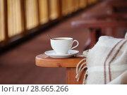 Купить «cup of coffee and plaid on terrace», фото № 28665266, снято 20 июня 2017 г. (c) Майя Крученкова / Фотобанк Лори