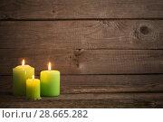 Купить «green candles on dark wooden background», фото № 28665282, снято 14 ноября 2017 г. (c) Майя Крученкова / Фотобанк Лори