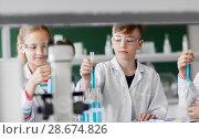 Купить «kids with test tubes studying chemistry at school», фото № 28674826, снято 19 мая 2018 г. (c) Syda Productions / Фотобанк Лори