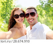 Купить «smiling couple wearing sunglasses making selfie», фото № 28674910, снято 23 июля 2014 г. (c) Syda Productions / Фотобанк Лори