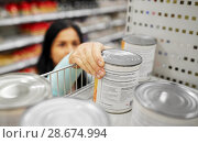 Купить «woman taking can with food from shelf at grocery», фото № 28674994, снято 2 ноября 2016 г. (c) Syda Productions / Фотобанк Лори