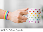Купить «hand with cup of cacao and gay awareness wristband», фото № 28675030, снято 14 ноября 2017 г. (c) Syda Productions / Фотобанк Лори