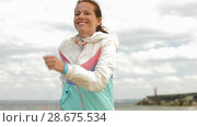 Купить «woman with fitness tracker running along beach», видеоролик № 28675534, снято 25 июня 2018 г. (c) Syda Productions / Фотобанк Лори
