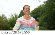 Купить «woman with earphones running at park», видеоролик № 28675550, снято 25 июня 2018 г. (c) Syda Productions / Фотобанк Лори