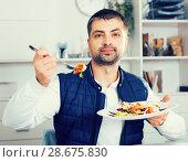 Купить «Portrait of young man eating vegetable salad», фото № 28675830, снято 25 декабря 2017 г. (c) Яков Филимонов / Фотобанк Лори
