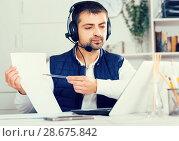 Купить «Young man call centre operator with headphones working», фото № 28675842, снято 25 декабря 2017 г. (c) Яков Филимонов / Фотобанк Лори